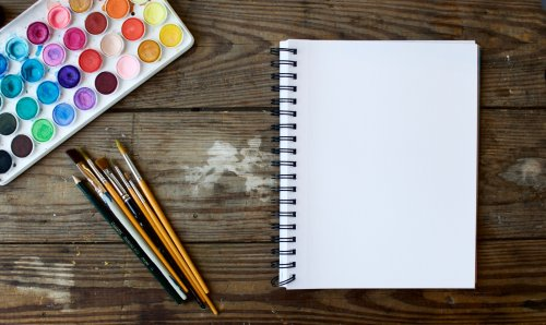a blank spiral notebook, unlined, lies next to a pile of paintbrushes and a used watercolor set on a wood table